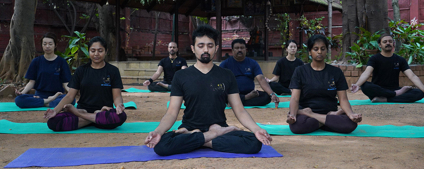Mimi Parthasarathy with her team in the Padmasana or Lotus Position